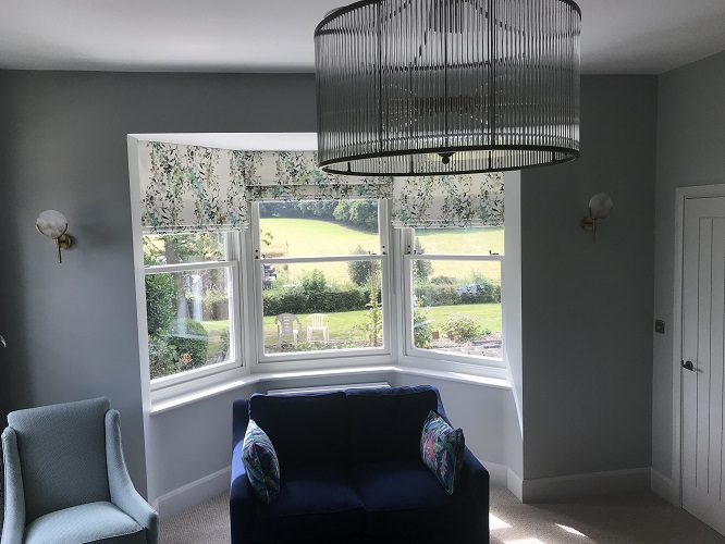 Cascade roman blinds in bay window